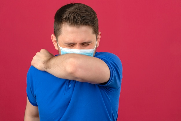 Young man wearing blue polo shirt in medical protective mask sneezing coughing into his arm or elbow to prevent spread covid-19coronavirus over isolated pink wall