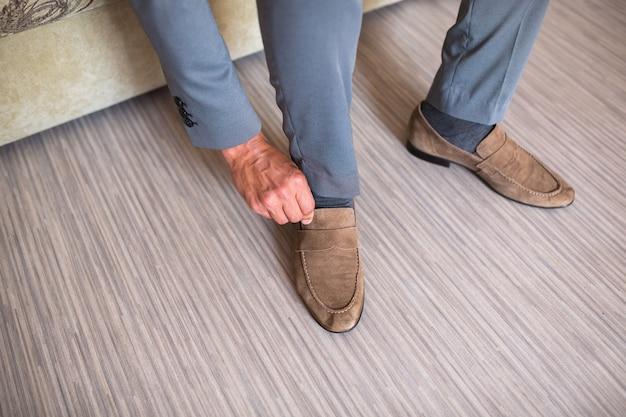 스위트룸과 회색 바지와 함께 갈색 샤무아 신발을 신고 있는 젊은 남자. 오래 된 우아한 신발과 함께 앉아 hipster 남자입니다. 끈에 대한 주요 초점