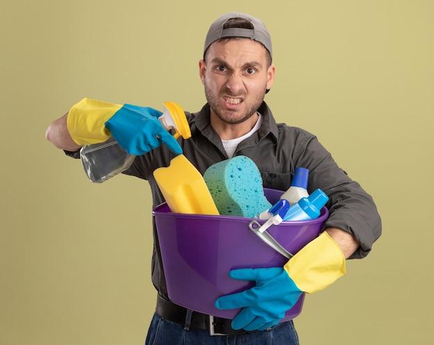 カジュアルな服とゴム手袋の帽子をかぶった若い男が掃除道具と掃除スプレーでバケツを保持している緑の壁の上に立って見て不機嫌になっている怒った顔