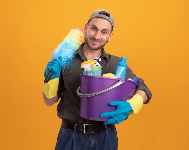 オレンジ色の壁の上に立って掃除する準備ができて笑顔に見えるクリーニングツールとカラフルなダスターでバケツを保持しているゴム手袋でカジュアルな服とキャップを身に着けている若い男