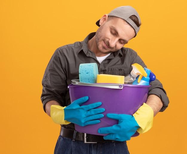 Молодой человек в повседневной одежде и кепке в резиновых перчатках держит ведро с чистящими средствами и смотрит на инструменты с любовью, счастлив и доволен, стоя над оранжевой стеной