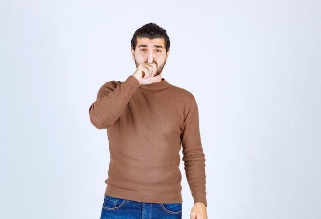 白い背景の上の唇に指で静かにするように求めるカジュアルな服を着ている若い男。高品質の写真