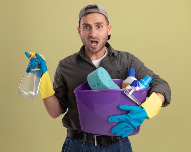 Giovane uomo che indossa abiti casual e berretto in guanti di gomma che tiene secchio con strumenti di pulizia e spray per la pulizia che sembra essere confuso in piedi sopra la parete verde