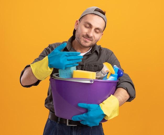 Giovane che indossa abiti casual e berretto in guanti di gomma che tiene secchio con strumenti di pulizia inalando piacevole aroma fresco in piedi sopra la parete arancione