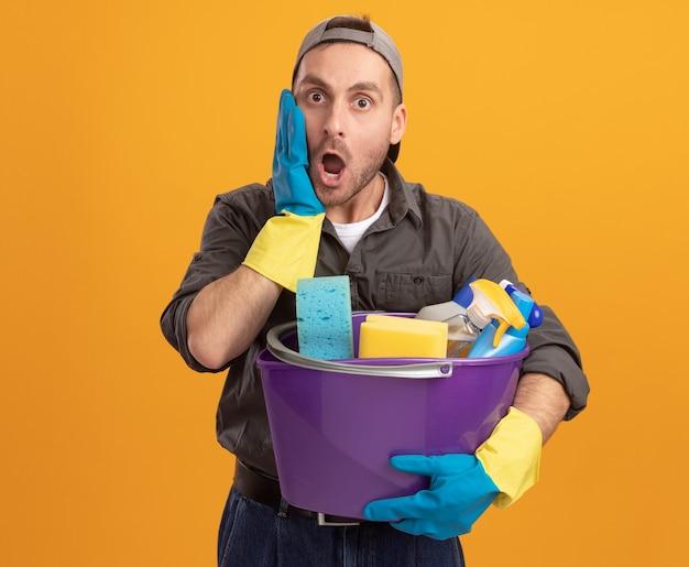 Giovane uomo che indossa abiti casual e berretto in guanti di gomma che tiene secchio con strumenti di pulizia guardando stupito e sorpreso in piedi sopra la parete arancione