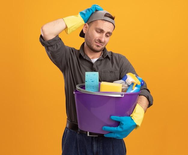 Giovane uomo che indossa abiti casual e berretto in guanti di gomma che tiene secchio con strumenti di pulizia che sembra confuso e scontento con la mano sulla sua testa in piedi sopra la parete arancione