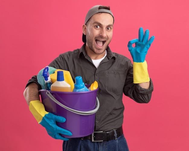 Giovane uomo che indossa abiti casual e berretto in guanti di gomma che tiene secchio con strumenti di pulizia guardando sorridente allegramente mostrando segno ok in piedi sopra la parete rosa