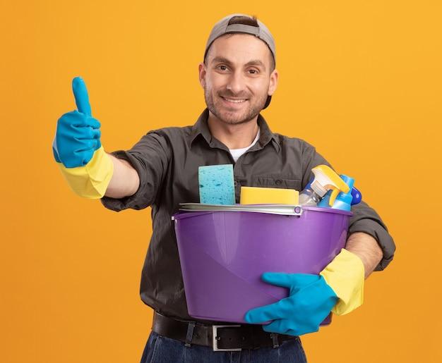 Giovane uomo che indossa abiti casual e berretto in guanti di gomma che tiene secchio con strumenti di pulizia guardando sorridente fiducioso che mostra i pollici in su in piedi sopra la parete arancione