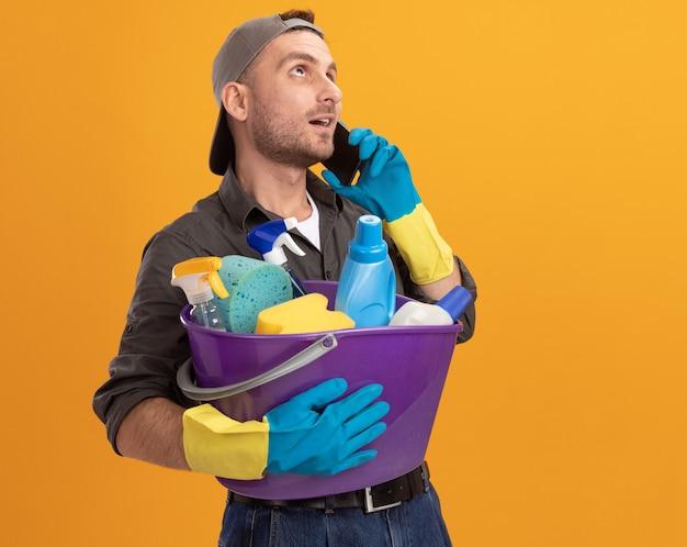 Giovane uomo che indossa abiti casual e berretto in guanti di gomma che tiene secchio con strumenti di pulizia che osserva in su sorridente fiducioso mentre parla al telefono cellulare in piedi sopra la parete arancione