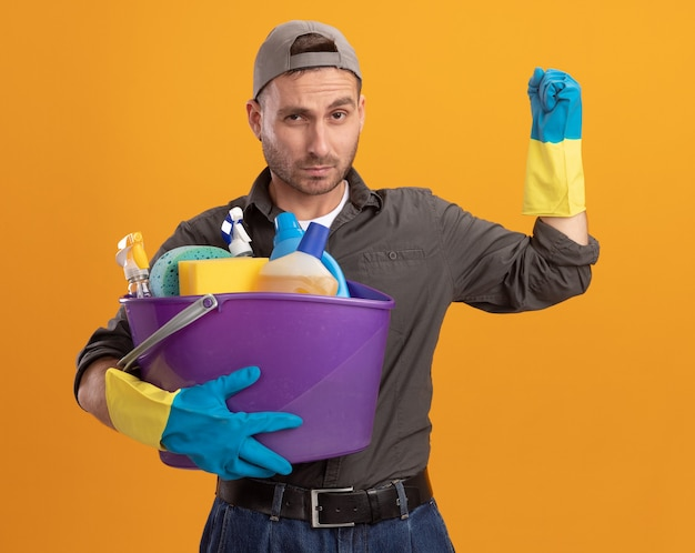 Giovane uomo che indossa abiti casual e berretto in guanti di gomma che tiene secchio con strumenti di pulizia guardando con faccia seria alzando il pugno in piedi sopra la parete arancione