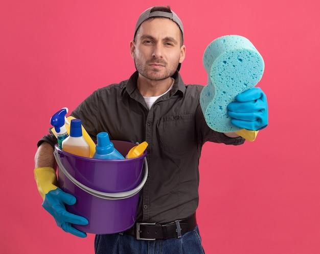 Giovane uomo che indossa abiti casual e berretto in guanti di gomma che tiene secchio con strumenti di pulizia che mostra spugna guardando con faccia seria in piedi sopra la parete rosa