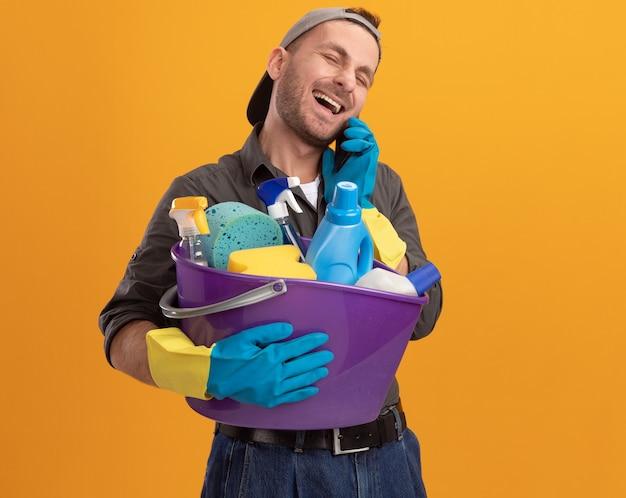 Giovane uomo che indossa abiti casual e berretto in guanti di gomma che tiene secchio con strumenti di pulizia sorridendo felice e allegro mentre parla al telefono cellulare in piedi sopra la parete arancione