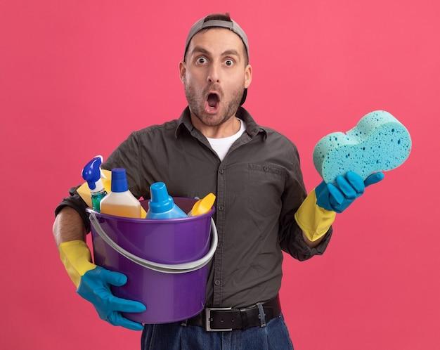 Giovane uomo che indossa abiti casual e berretto in guanti di gomma che tiene secchio con strumenti di pulizia e spugna guardando stupito e sorpreso in piedi sopra il muro rosa