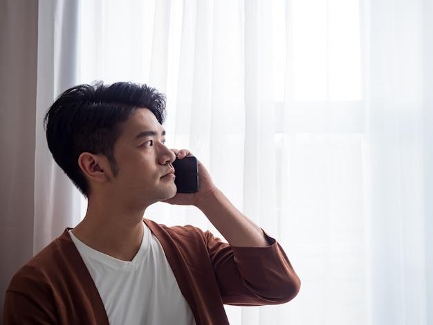Молодой человек в повседневной одежде и разговаривает по мобильному телефону