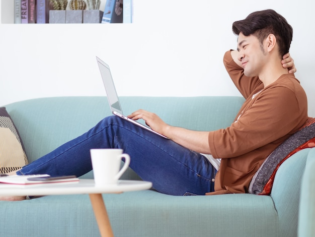 Young man wearing casual clothes and using laptop