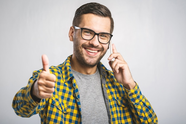 Young man wearing a casual shirt and eyeglasses using the phone