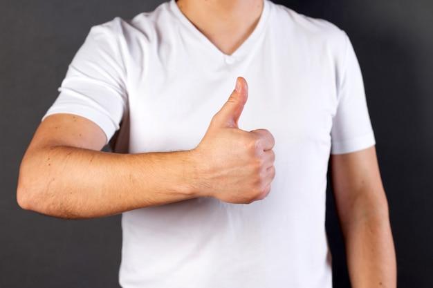 엄지 손가락을 보여주는 캐주얼 흰색 tshirt 입고 젊은 남자