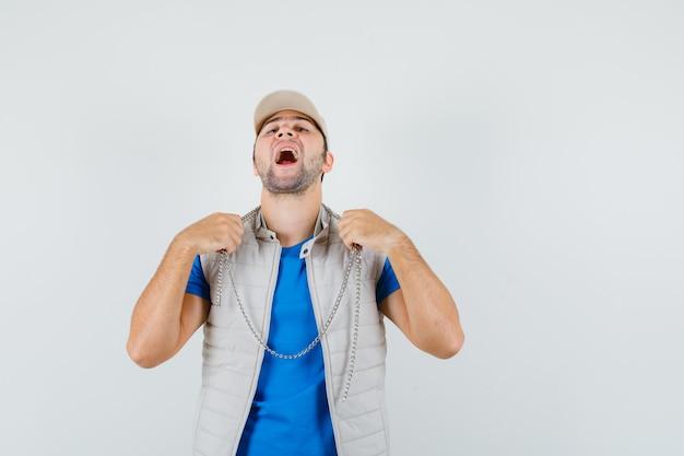 Giovane uomo che indossa collana a catena in t-shirt, giacca, berretto e guardando orgoglioso. vista frontale.