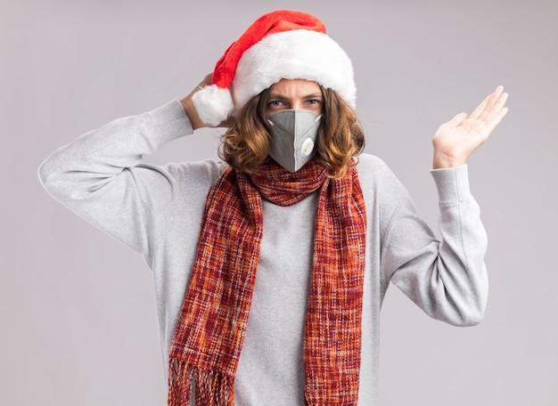 クリスマスのサンタの帽子と首に暖かいスカーフを身に着けている顔の保護マスクを身に着けている若い男は、白い壁の上に立って混乱し、不快になりました
