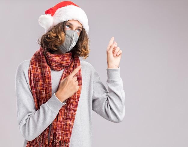 クリスマスのサンタの帽子と白い壁の上に立っている側に人差し指で指している彼の首の周りに暖かいスカーフと顔の保護マスクを身に着けている若い男