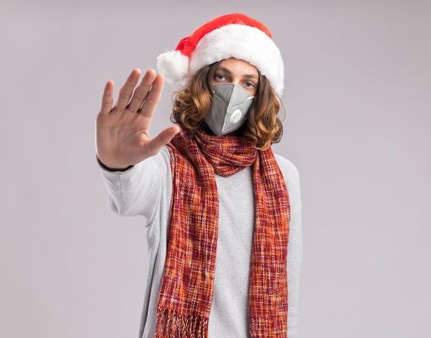 クリスマスのサンタの帽子と顔の保護マスクを身に着けている若い男は、白い壁の上に立っている手で停止ジェスチャーをする深刻な顔で彼の首に暖かいスカーフを持っています