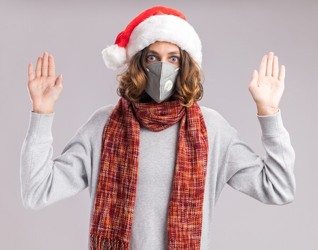 クリスマスのサンタの帽子と彼の首の周りに暖かいスカーフと顔の保護マスクを身に着けている若い男は、白い壁の上に立って降伏で手を上げることを心配しました