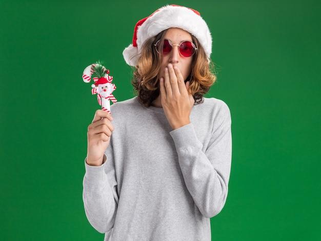 크리스마스 산타 모자와 카메라를보고 크리스마스 사탕 지팡이를 들고 빨간 안경을 착용하는 젊은 남자는 녹색 배경 위에 서 손으로 입을 덮고 충격