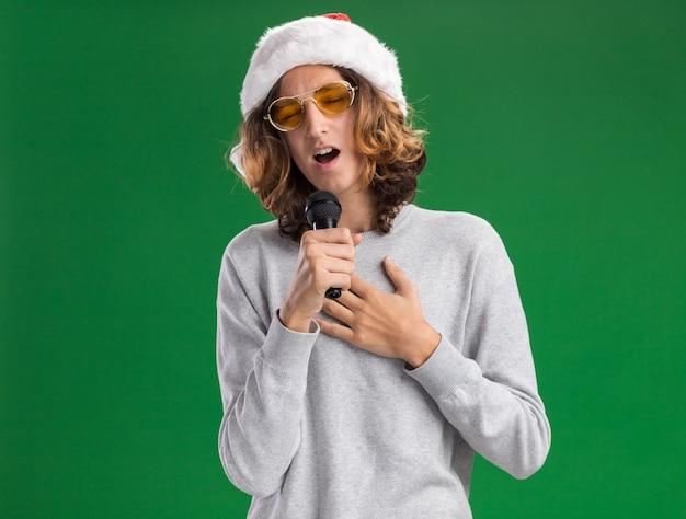 緑の背景の上に立っている前向きな感情を感じてマイクを歌っているクリスマスサンタの帽子と黄色いメガネを身に着けている若い男