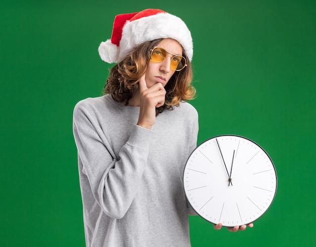 クリスマスのサンタの帽子と緑の背景の上に立って困惑して見上げる壁時計を保持している黄色いメガネを身に着けている若い男