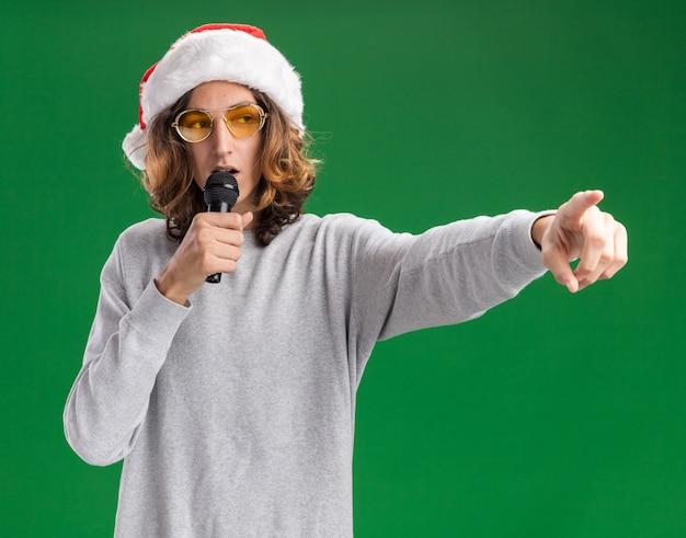 クリスマスのサンタの帽子と黄色いメガネを身に着けている若い男が緑の背景の上に立っている側に人差し指で指しているマイクに向かって話します