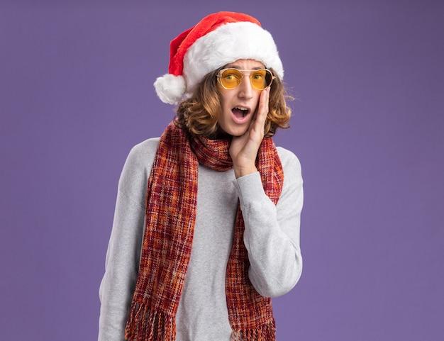 그의 목 주위에 따뜻한 스카프와 함께 크리스마스 산타 모자와 노란색 안경을 착용하는 젊은 남자는 깜짝 놀라게하고 보라색 벽 위에 서서 놀랐습니다.