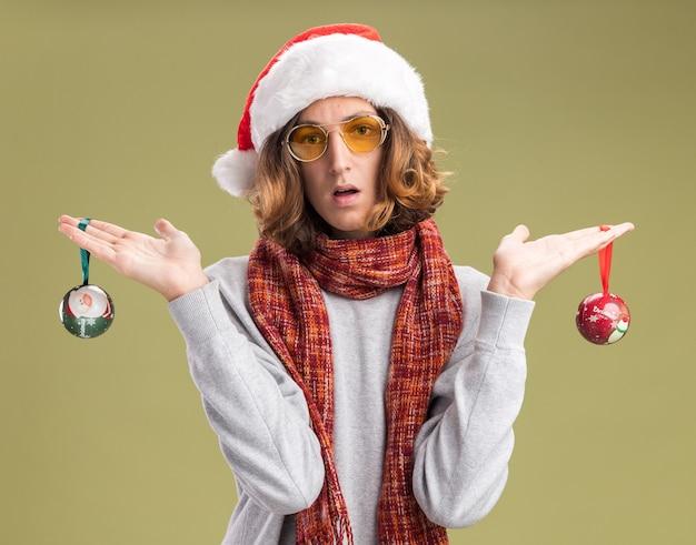 Молодой человек в новогодней шапке санта-клауса и желтых очках с теплым шарфом на шее держит в замешательстве рождественские шары, стоя у зеленой стены