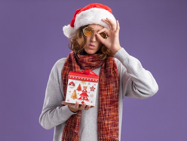 Молодой человек в рождественской шляпе санта-клауса и желтых очках с теплым шарфом на шее держит рождественский подарок, делает знак ок, глядя сквозь этот знак, стоящий над фиолетовой стеной