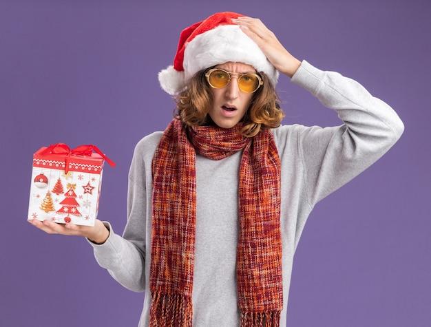 クリスマスのサンタの帽子と彼の首の周りに暖かいスカーフと黄色のメガネを身に着けている若い男は、紫色の背景の上に立っている頭の上に手で混乱しているように見えるクリスマスの贈り物を保持しています