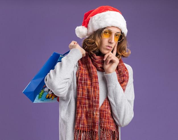 クリスマスのサンタの帽子と彼の首の周りに暖かいスカーフと黄色のメガネを身に着けている若い男は、紫色の背景の上に立っている深刻な顔でカメラを見て贈り物とクリスマス紙袋を保持