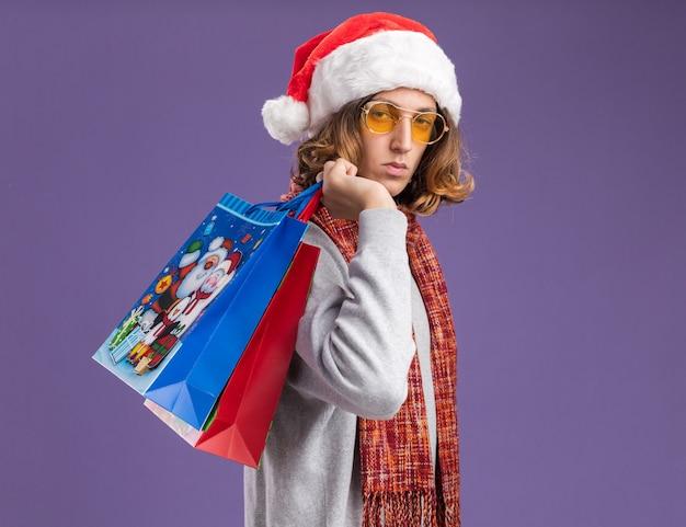 보라색 벽 위에 서 심각한 얼굴로 선물 크리스마스 종이 가방을 들고 그의 목에 따뜻한 스카프와 함께 크리스마스 산타 모자와 노란색 안경을 착용하는 젊은 남자