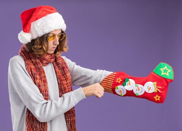 Молодой человек в рождественской шапке санта-клауса и желтых очках с теплым шарфом на шее держит рождественский чулок, смущенно глядя на него, стоя на фиолетовом фоне