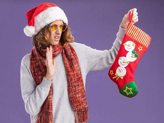 Молодой человек в рождественской шапке санта-клауса и желтых очках с теплым шарфом на шее держит рождественский чулок, глядя на него с отвращением на фиолетовом фоне