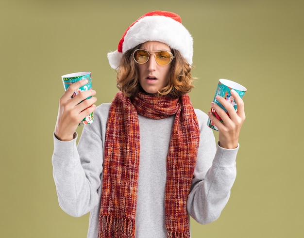 녹색 배경 위에 서있는 의심을 갖는 혼란 찾고 다채로운 종이 컵을 들고 그의 목에 따뜻한 스카프와 크리스마스 산타 모자와 노란색 안경을 착용하는 젊은 남자