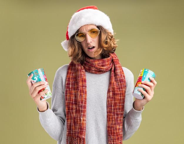 緑の背景の上に立っている疑いを持って混乱しているように見えるカラフルな紙コップを持っている彼の首の周りに暖かいスカーフとクリスマスサンタ帽子と黄色いメガネを身に着けている若い男