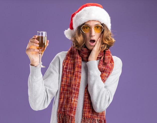 クリスマスのサンタの帽子と黄色いメガネを首に暖かいスカーフを身に着けている若い男は、紫色の壁の上に立って驚いて驚いたシャンパンのガラスを保持しています