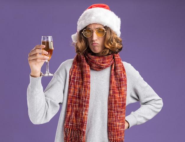 クリスマスのサンタの帽子と黄色いメガネを身に着けている若い男が首に暖かいスカーフを持ってシャンパンのグラスを持ってそれを見て困惑している紫色の壁の上に立っている