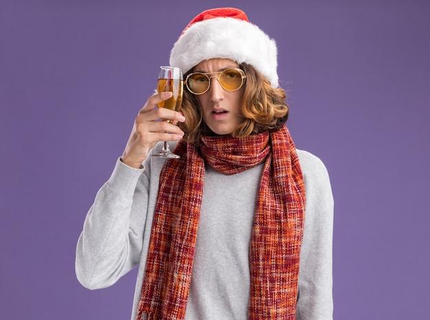 クリスマスのサンタの帽子と黄色いメガネを首に暖かいスカーフを身に着けている若い男は、紫色の壁の上に立って心配しているシャンパンのガラスを保持しています