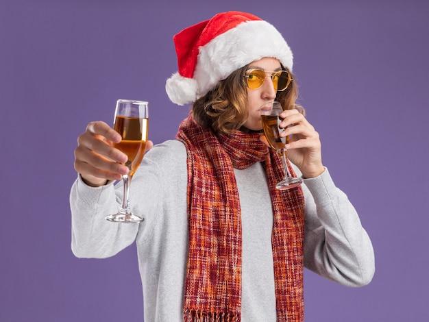 보라색 벽 위에 행복하고 긍정적 인 서 샴페인 잔을 들고 그의 목에 따뜻한 스카프와 크리스마스 산타 모자와 노란색 안경을 착용하는 젊은 남자