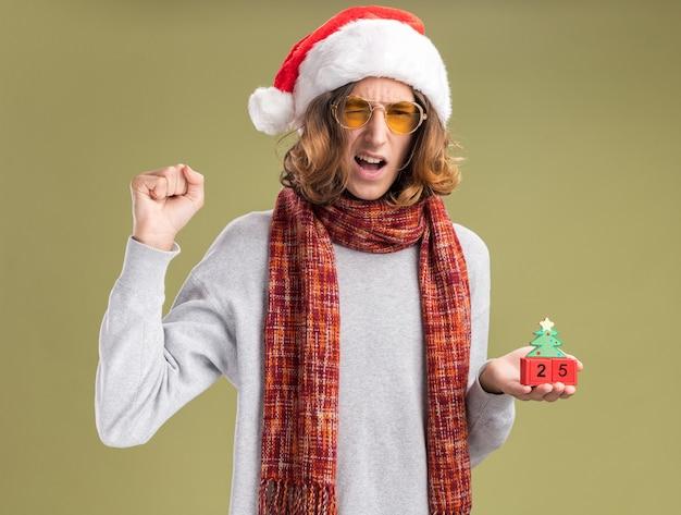 Молодой человек в рождественской шапке санта-клауса и желтых очках с теплым шарфом на шее держит игрушечные кубики с датой двадцать пять, сжимая кулак, счастлив и взволнован, стоя на зеленом фоне