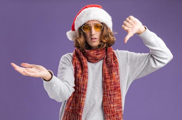 紫色の背景の上に立っている手の腕を提示して親指を下に表示して混乱しているカメラを見て彼の首の周りに暖かいスカーフとクリスマスサンタ帽子と黄色いメガネを身に着けている若い男