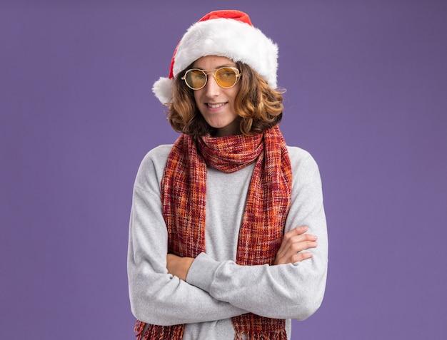 크리스마스 산타 모자와 노란색 안경을 착용하는 젊은 남자가 팔에 자신감이 웃고 카메라를보고 그의 목에 따뜻한 스카프와 함께 보라색 배경 위에 서 교차