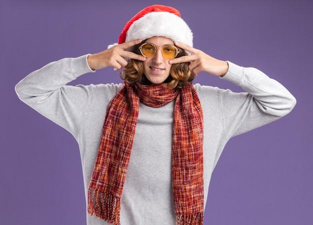 紫色の背景の上に立っている彼の目の近くにvサインを示しているカメラの笑顔を見て首の周りに暖かいスカーフとクリスマスサンタ帽子と黄色いメガネを身に着けている若い男