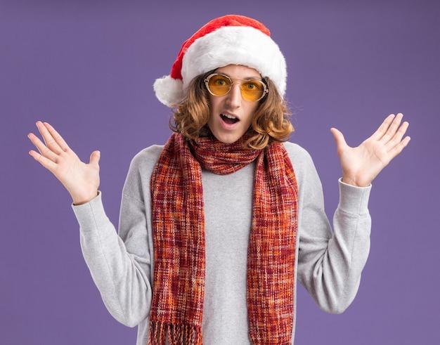 크리스마스 산타 모자와 노란색 안경을 착용하는 젊은 남자가 카메라를보고 그의 목에 따뜻한 스카프로 노란색 안경을 착용하고 보라색 배경 위에 서있는 팔에 놀라고 행복합니다.