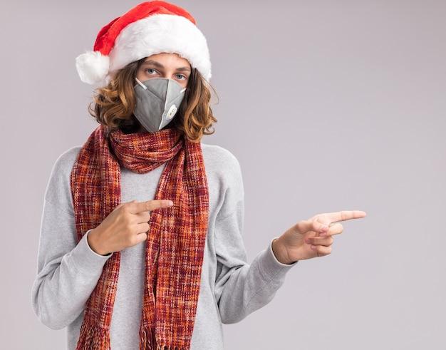 Giovane uomo che indossa il cappello di babbo natale e maschera protettiva per il viso con sciarpa calda intorno al collo guardando la telecamera puntando con le dita indice al lato in piedi su sfondo bianco